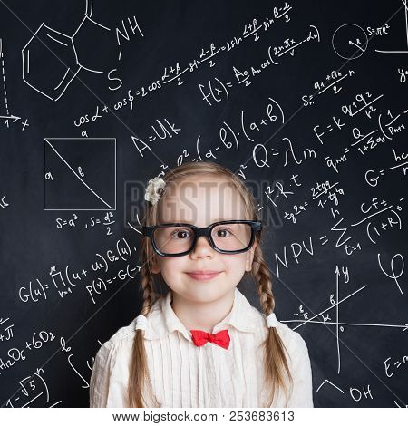 Little Genius. Smart Little Girl Math Student On School Blackboard Background With Hand Drawings Sci