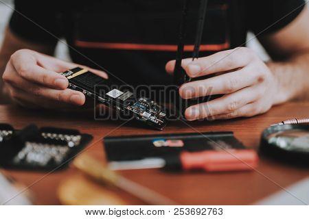 Close Up. Young Man Repairing Mobile Phone. Repair Shop. Worker With Tools. Magnifying Glass. Digita