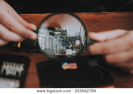 Close Up. Young Man Repairing Mobile Phone. Repair Shop. Worker With Tools. Magnifying Glass. Digita
