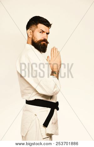 Karate man strict face image photo free trial bigstock karate man with strict face in uniform japanese martial arts concept taekwondo master with black belt holds hands together in greeting m4hsunfo