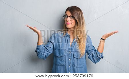 Young adult woman over grunge grey wall wearing glasses clueless and confused expression with arms and hands raised. Doubt concept.