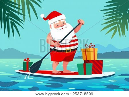 Cute Santa Claus In Shorts And T-shirt On A Stand Up Paddle Board With Gifts, Against Tropical Ocean