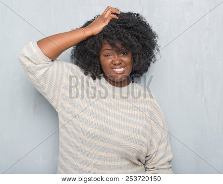 Young african american plus size woman over grey grunge wall wearing a sweater confuse and wonder about question. Uncertain with doubt, thinking with hand on head. Pensive concept.