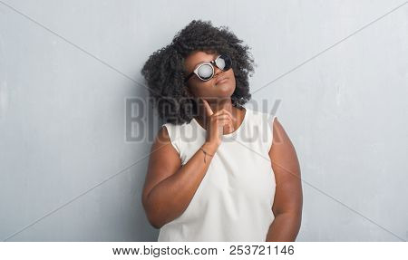 Young african american plus size woman over grey grunge wall wearing fashion sunglasses with hand on chin thinking about question, pensive expression. Smiling with thoughtful face. Doubt concept.