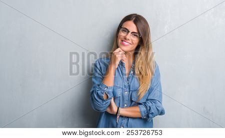 Young adult woman over grunge grey wall wearing glasses with hand on chin thinking about question, pensive expression. Smiling with thoughtful face. Doubt concept.
