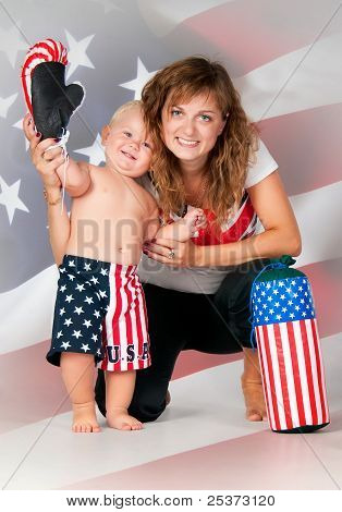 Smiling mom and son waving his hand on American flag background. Boy in boxer shorts with  boxing gl