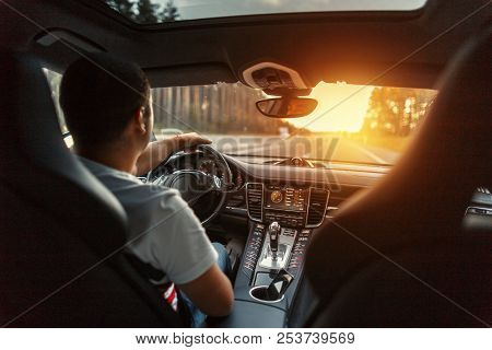 Man In A Premium Car With An Interior Is Driving At Sunset. Concept Travel By Car
