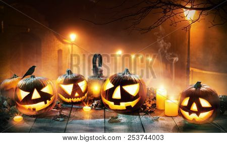 Scary horror background with halloween pumpkins jack o lantern, placed on wooden deck. Old town street on background with glowing lamps. Halloween spooky background.