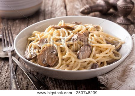 A Bowl Of Delicious Pasta Alfredo With Mushrooms On A Rustic Table Top.