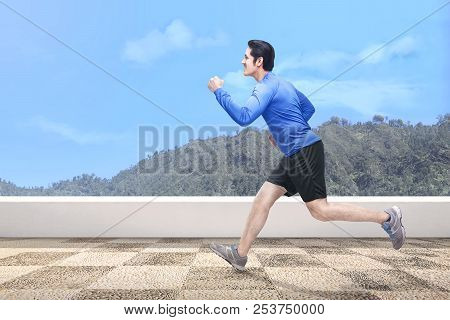 Handsome Asian Man Running Outdoors With Green Hills Background