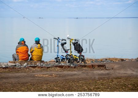 Two Sporty Fully-equipped Cyclists Sitting On A Shore With Bikes And Looking At The Landscape And Se