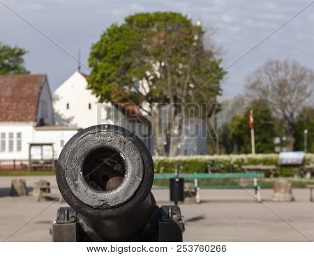 Closeup View Of An Old Cannons. Village, Buildings In The Background.