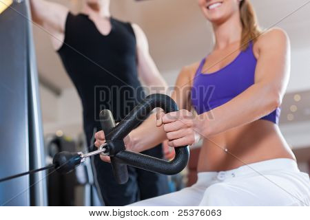 Young couple exercising in gym on different power machines to strengthen the muscles; the man is personal trainer