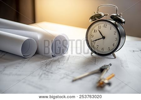 Clock And Compass Tool On Architectural Drawing Plan Of House Project, Blueprint Rolls On Working Ta
