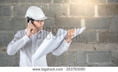 Asian Male Engineer Or Architect Holding Blueprints Or Architectural Drawing While Using Smartphone