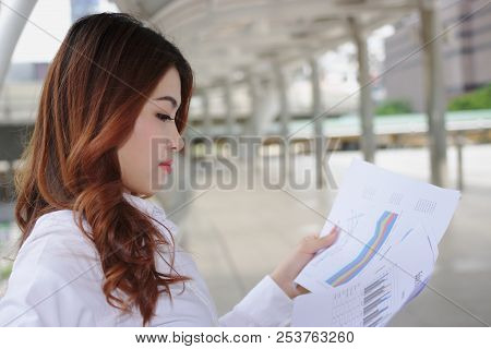 Attractive Young Asian Business Woman Analyzing Charts Or Paperwork At Outside Office. Selective Foc