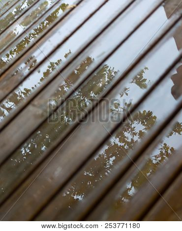 Wet Cottage Deck. Reflections In Puddles On Wooden Planks After Summer Rain. Background