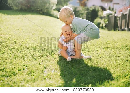 Happy Children Play On Nature Outdoors. Brother And Sister.