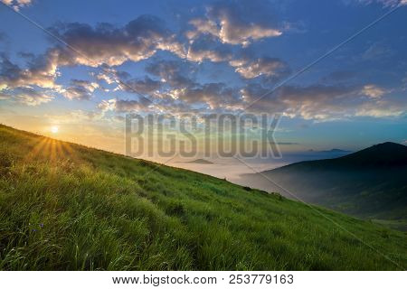 Mountain Landscape In Nice Weather At Sunrise. Green Grassy Steep Hill, Foggy Valley And Distant Mou
