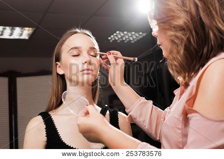Makeup Artist Appling A Primer On An Eyelid Of A Young Beautiful Woman Using A Brush Before Dabbing
