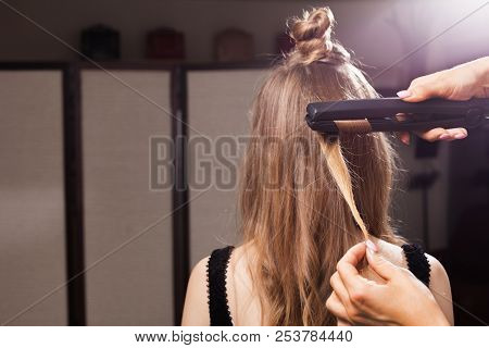 professional hairdresser curling a hair strand of a model with a topknot in a beauty salon. concept of stylist training poster