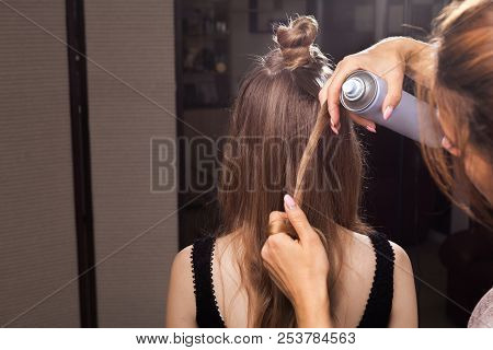 hairdresser fixing hairstrand of a young beautiful model with a coiffure using a hairspray in a beauty salon. concept of professional stylist studying poster