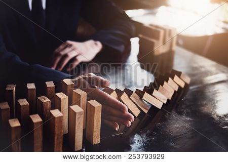Business Risk Control Concept, Businessman Protect Wooden Block Fall To Planning And Strategy In Ris