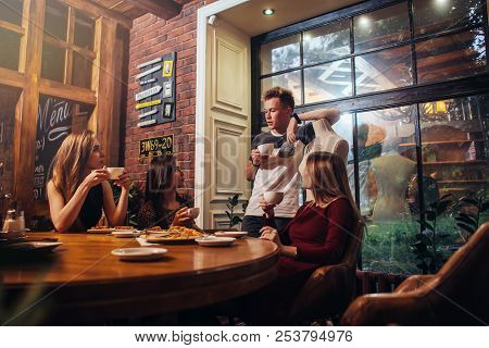 Serious Young People Sitting In A Fashionable Cafe Drinking Tea Discussing