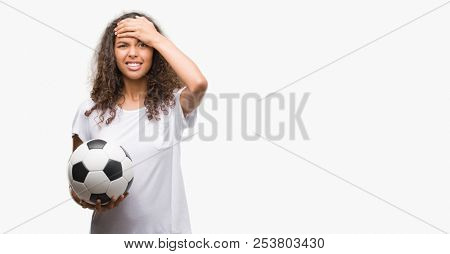 Young hispanic woman holding soccer football ball stressed with hand on head, shocked with shame and surprise face, angry and frustrated. Fear and upset for mistake.