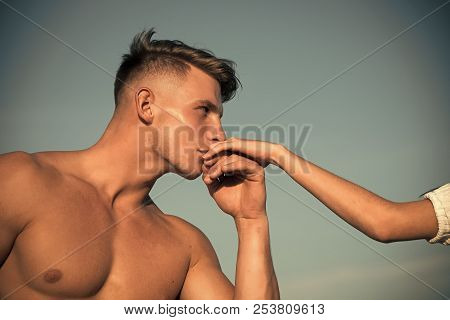 Athlete With Muscular Chest Kiss Female Hand On Sunny Day On Blue Sky. Romance, Love, Relations Conc