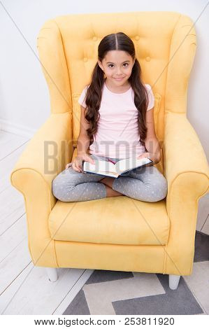 Reading useful hobby. Girl child sit yellow armchair read book. Kid cute bookworm. Pleasant time in cozy bedroom. Girl kid cute pajamas relax read fairytale book before sleep. Encourage useful habits poster