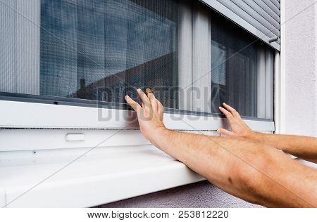 Screen On Window. Hands Holds Anti-insect Mosquito Net On Pvc Window