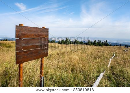 Wooden Multi Sign On The Top Of A Hill With Golden Grass In The Summer