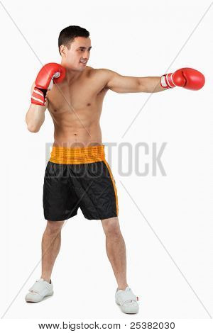 Side view of boxer hitting straight against a white background