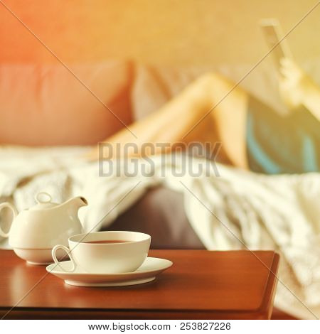 Cozy Home Interior With Teapot, Cup Of Tea And Woman Reading Ebook. Square, Toned