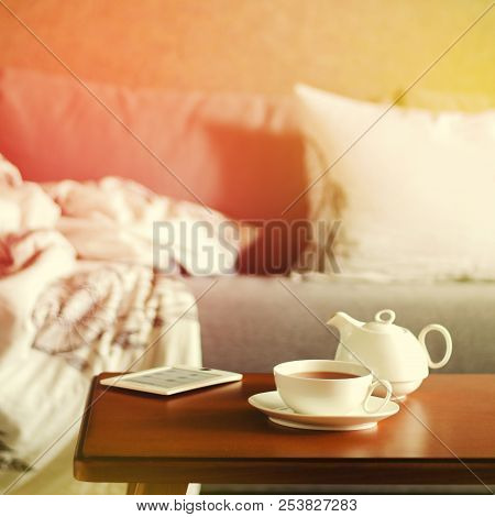 Cozy Home Interior With Teapot, Cup Of Tea And Ebook. Square, Toned