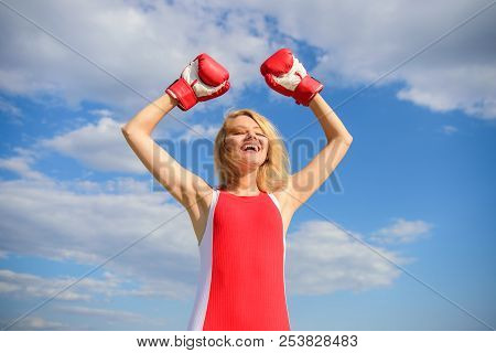 Woman boxing gloves raise hands blue sky background. Girl boxing gloves symbol struggle for female rights and liberties. Feminism promotion. Fight for female rights. Girl leader promoting feminism poster