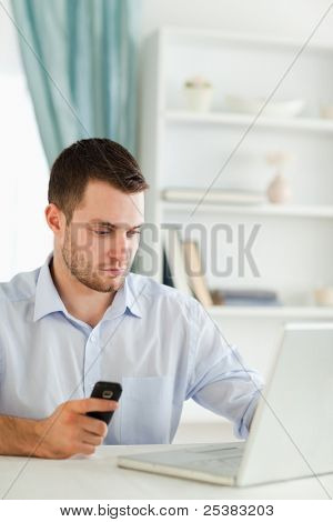 Young businessman holding cellphone while typing