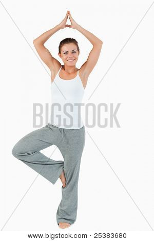 Portrait of a smiling woman in the Vrksasana position against a white background