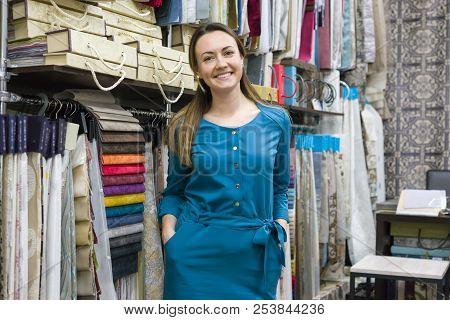 Portrait Of Happy Mature Woman Owner In Interior Fabrics Store, Background Fabric Samples. Small Bus