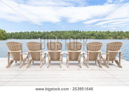 Row Of Muskoka Chairs On A Dock Looking Onto The Lake.