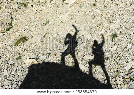 Two Shadows Of Photographers On The Earth Going Uphill With Up-raised Hands Screaming About Victory