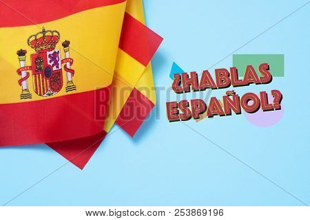 some flags of Spain and the question hablas espanol? do you speak Spanish? written in Spanish, on a blue background
