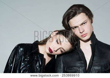 Girl With Make Up Lean On Male Shoulder, Grey Background. Couple On Calm Faces Dressed In Fashionabl