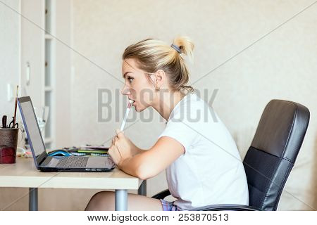 Beautiful Blonde Woman Working On Laptop At Home. She Is Thoughtful And Focused On Work. Freelance,