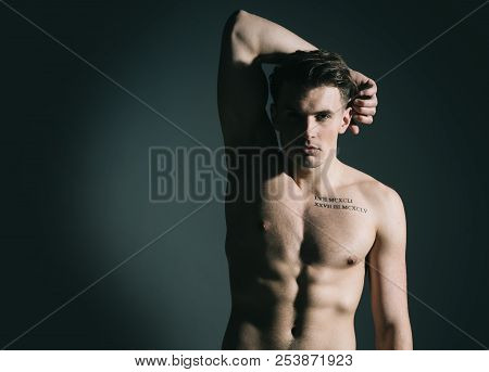 Man With Torso, Muscular Macho With Six Packs, Dark Background. Guy With Tattoo Looks Confident And
