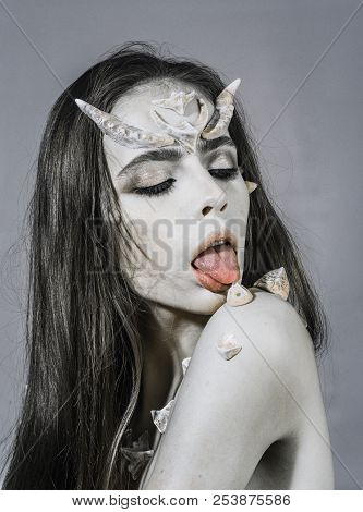 Tempting character. Woman with horns and thorns licking shoulder pink tongue fantasy creature. Halloween makeup. Girl with thorns as devil dragon magical creature. Girl with fantasy style makeup. poster