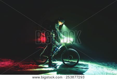 Extreme Bike Race In Winter Night. Cyclist On The Icy Way Covered By Fresh Snow. Cyclist Racer In Wi