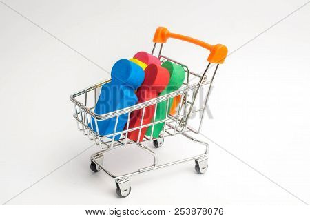 Colored People In A Trolley For A Supermarket. Concept Of Human Trafficking, Modern Slavery. Buying