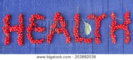 Word Health From Red Ripe Berries Of Schisandra On Dark Blue Background. Healthful Schisandra
